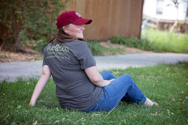 woman looking off into the distance wearing a pub dog branded maroon baseball cap and charcoal tshirt back
