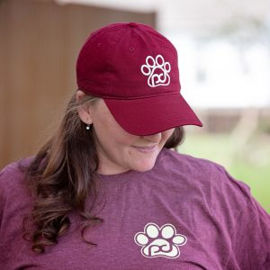 woman looking down wearing a pub dog branded maroon hat and maroon long sleeved shirt