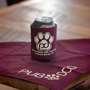 picture of a beer can in a pub dog branded koozie on top of a pub dog branded bandana